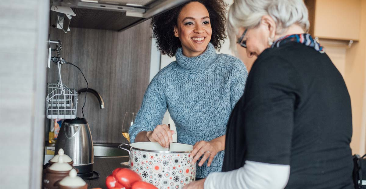 Woman helping to cook with older woman